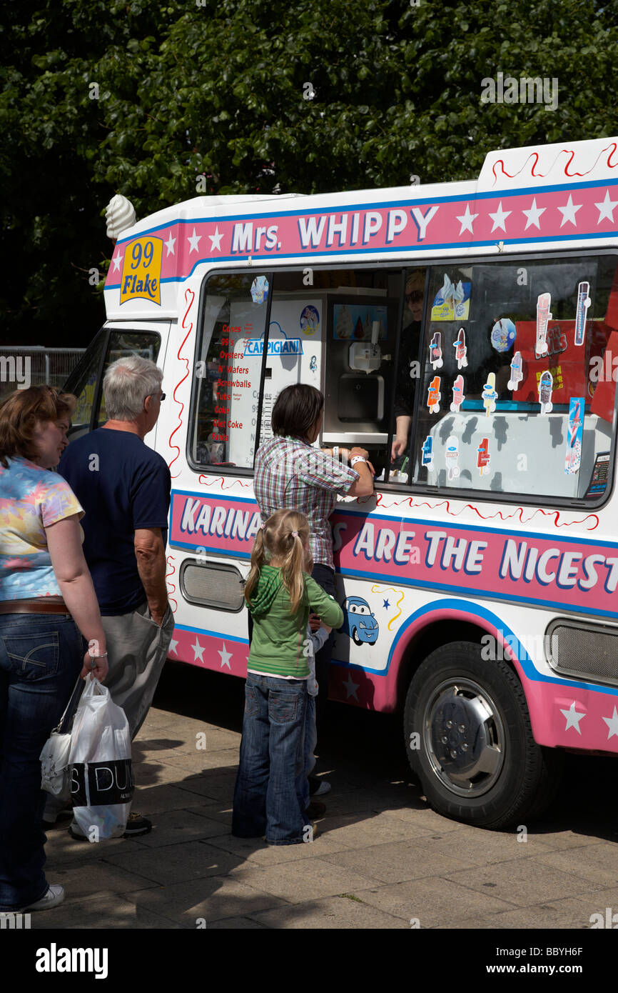 queue of people on a hot summer day waiting to buy ice cream from a mobile ice cream van county down northern ireland - Stock Image