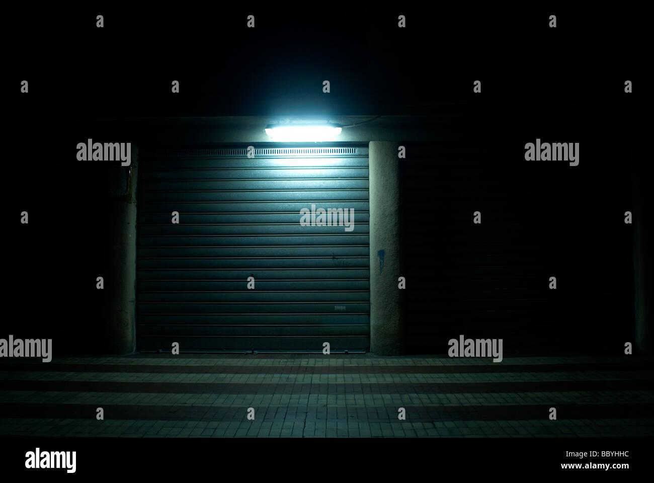 Dark urban passageway with shop closed up at night - Stock Image