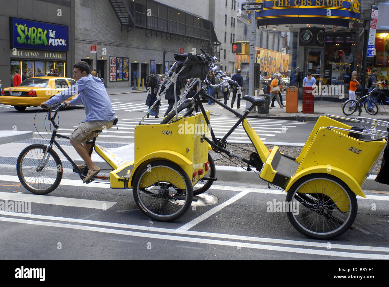6c3635e6d89 A pedicab driver tows another pedicab in midtown in New York - Stock Image