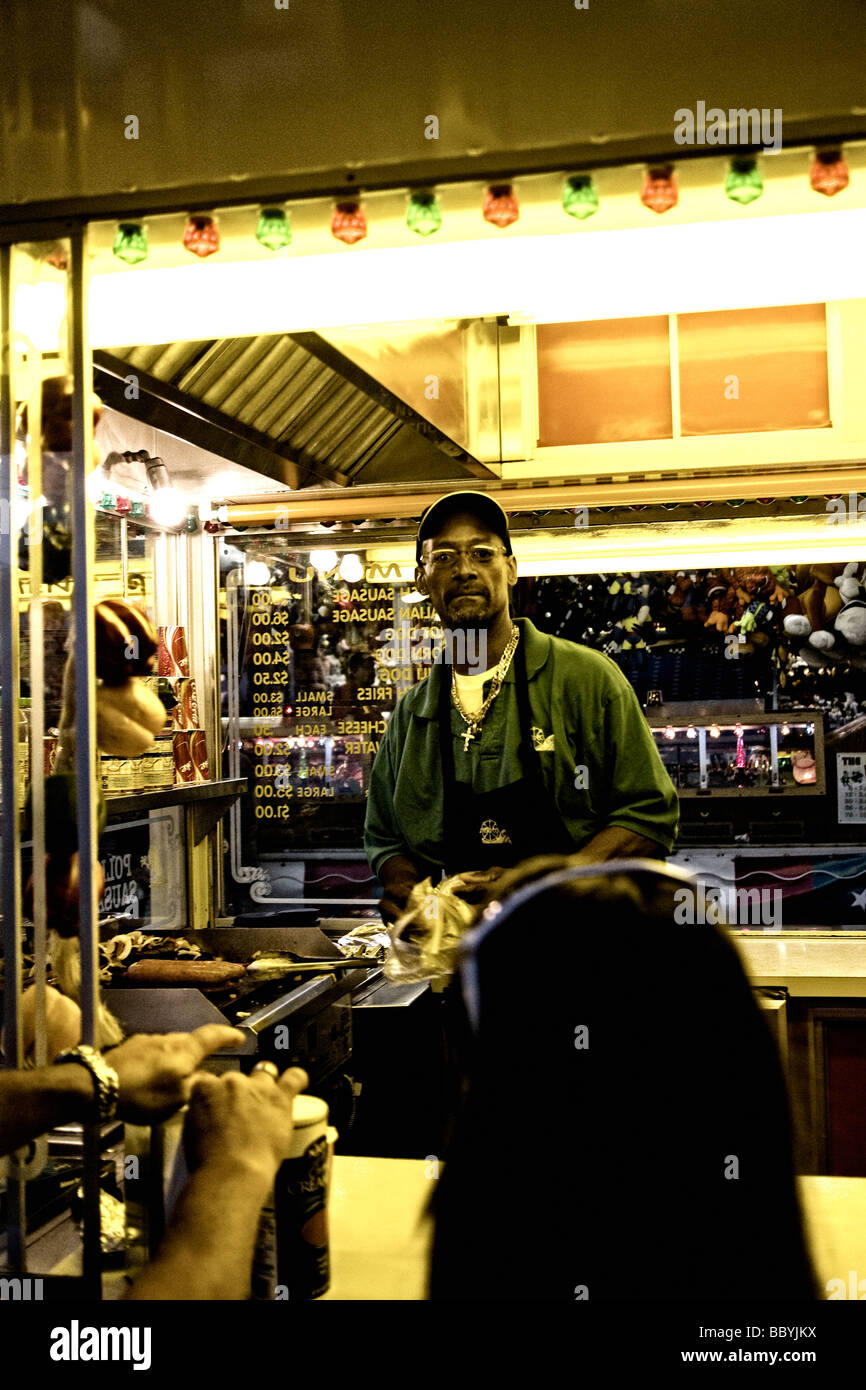 Man preparing food at concession stand at a festival - Stock Image