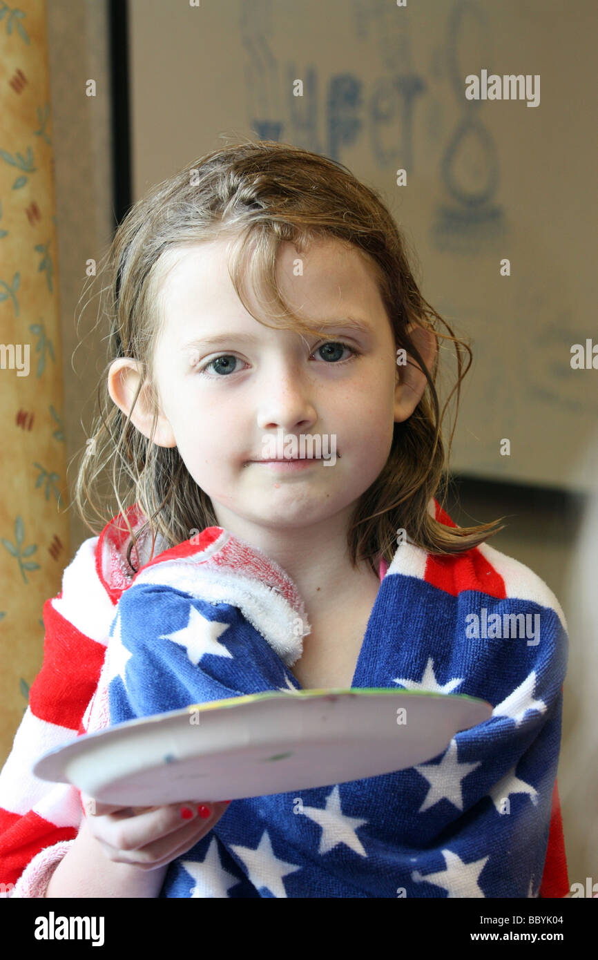 Girl wrapped in American flag towel with an empty plate - Stock Image