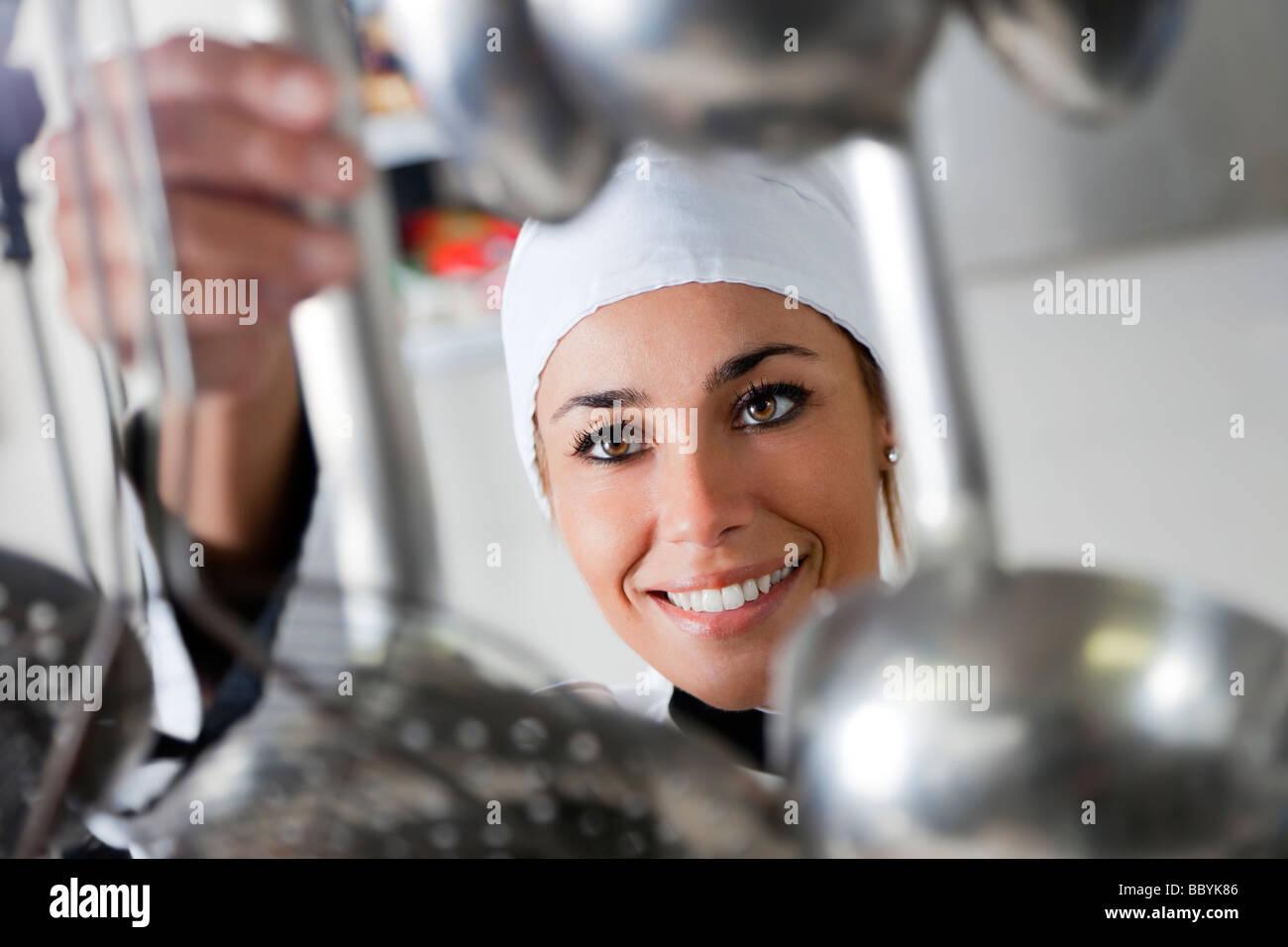 mid adult female chef taking kitchen utensil - Stock Image