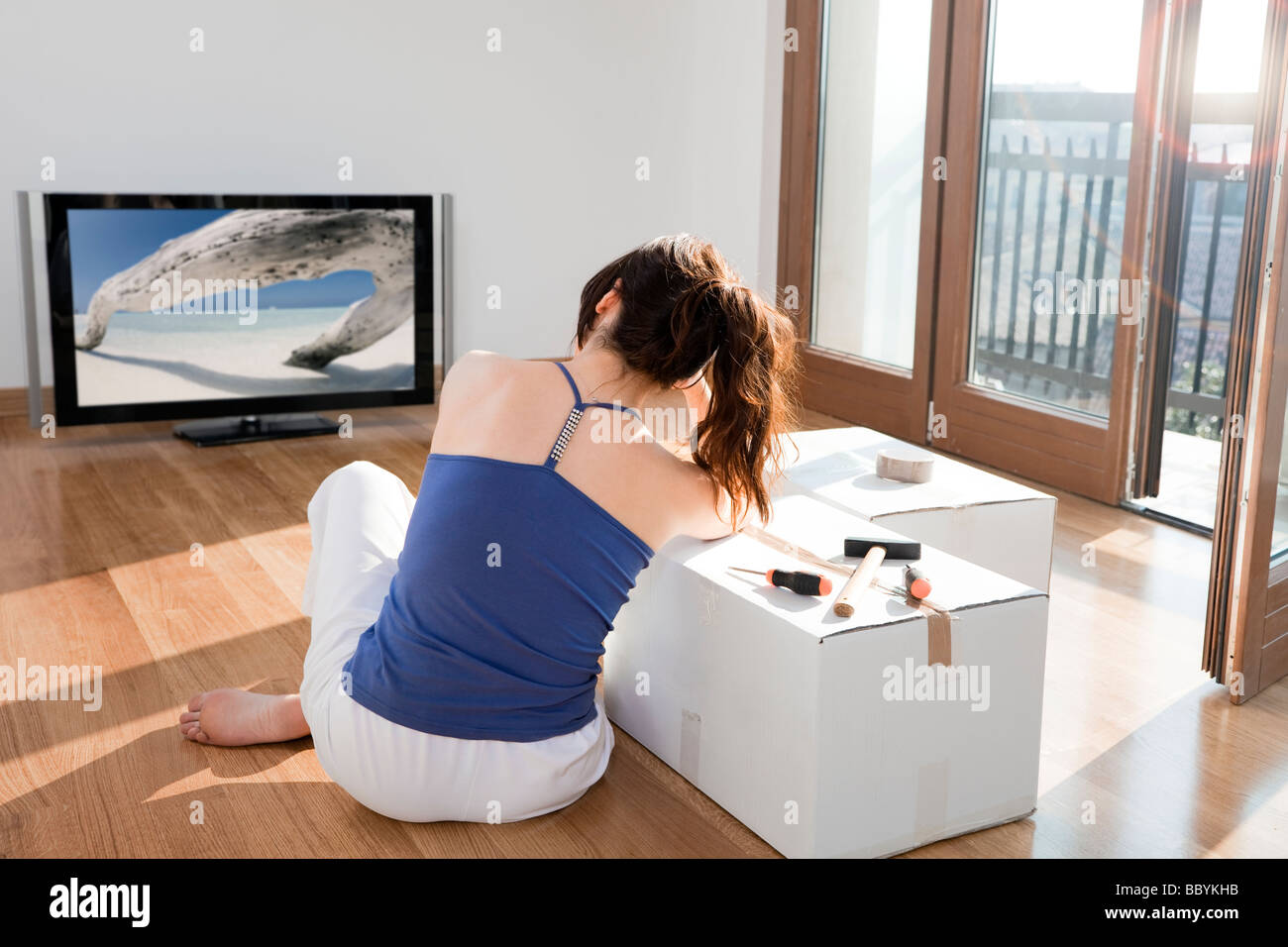 young woman moving house and sitting on floor, relaxing - Stock Image
