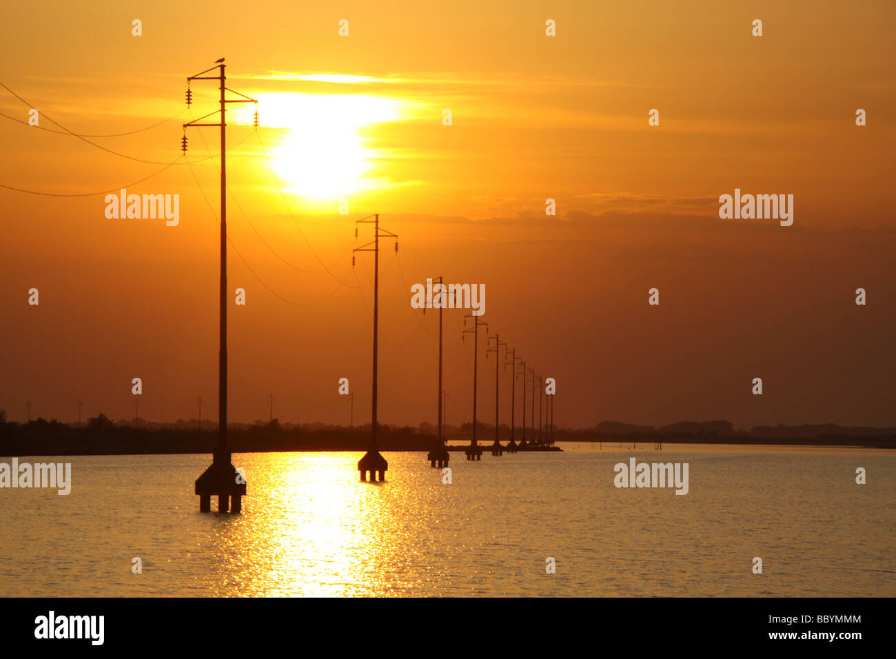 Sunset and silhouetted power cables pylons, supplying albarella island, italy - Stock Image