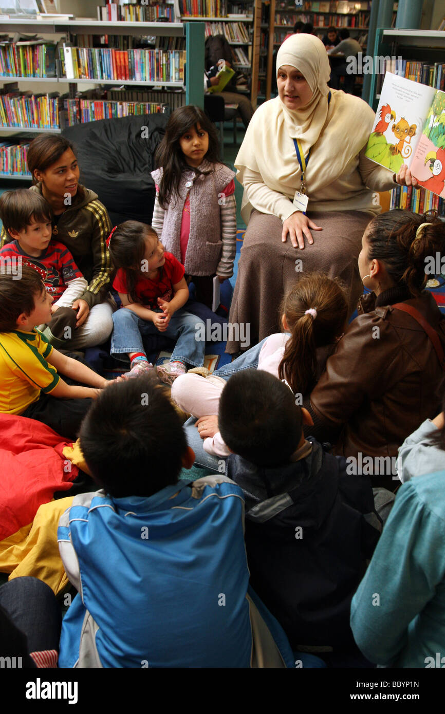 Librarian reading aa book to children in library - Stock Image