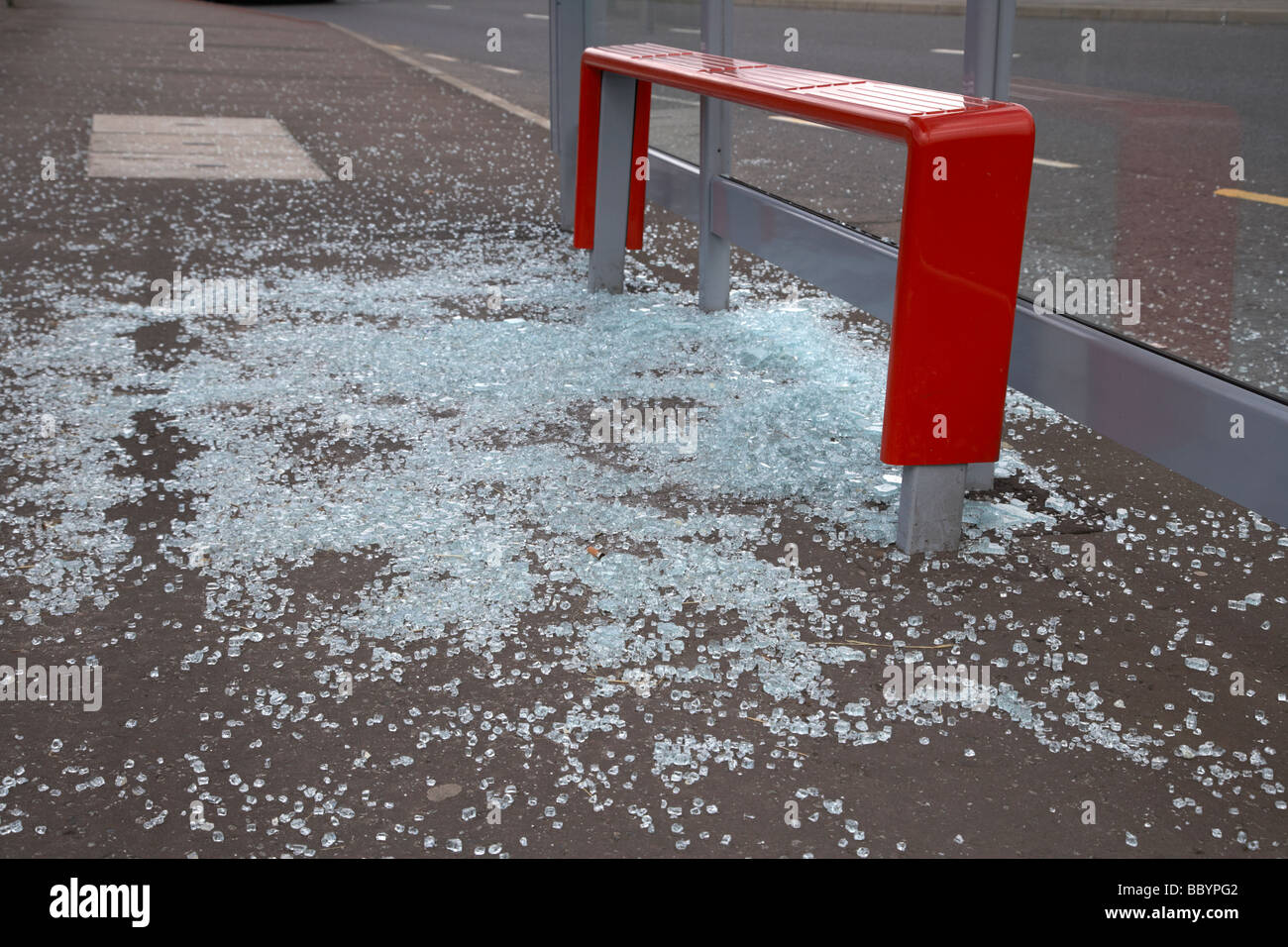 shattered glass lying on the ground from a vandalised bus shelter in northern ireland - Stock Image