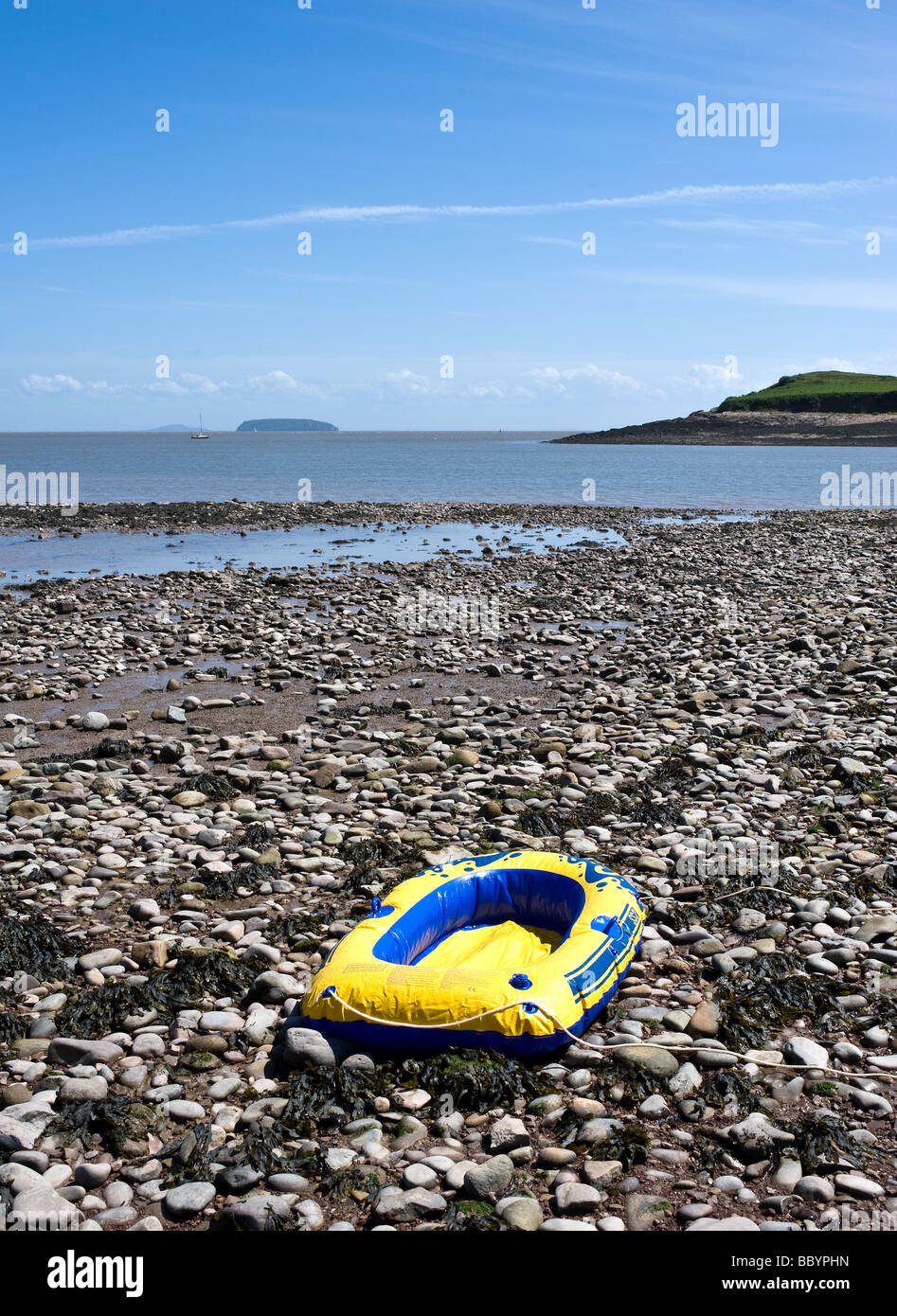 A punctured inflatable rubber dinghy abandoned on the pebble beach at Sully in South Wales. - Stock Image