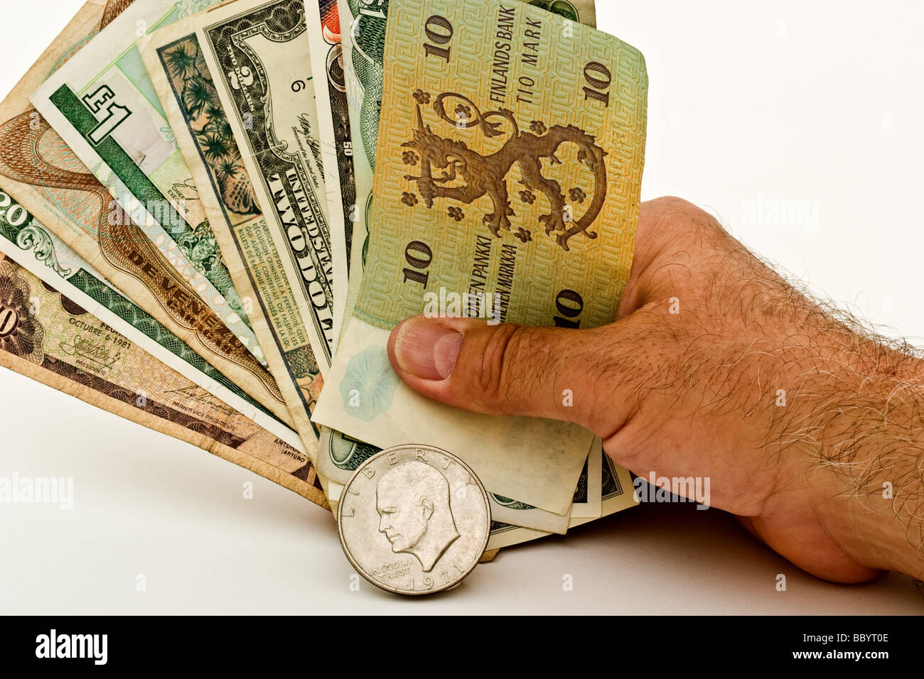 Hand holding currencies from a variety of countries behind an American silver dollar - Stock Image