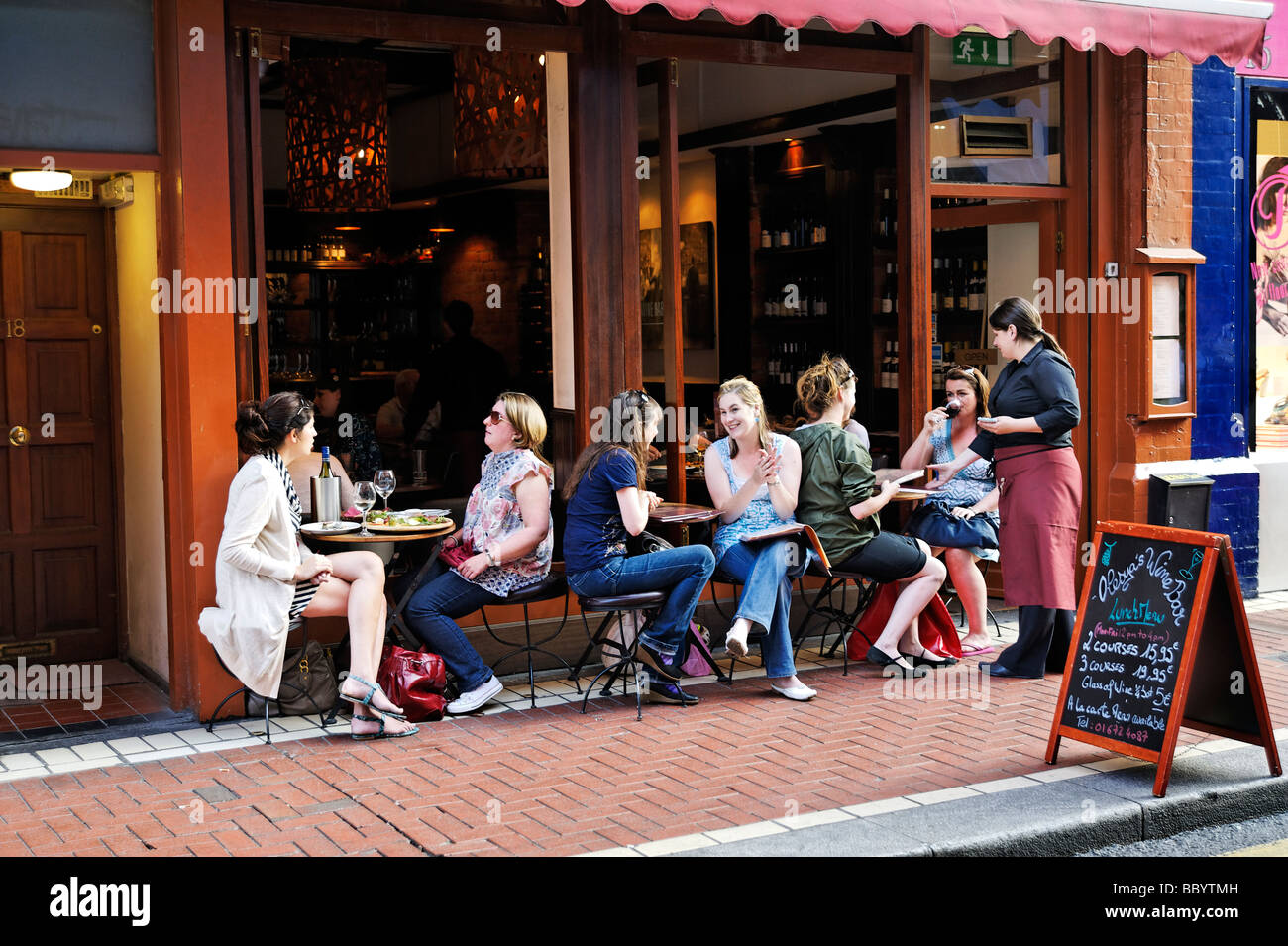 Group of women dinning alfresco in trendy cafe Dublin Republic of Ireland - Stock Image