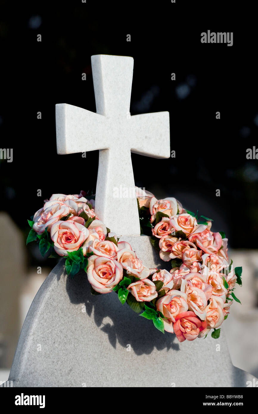 A cross on a gravestone adorned with a wreath of flowers - Stock Image