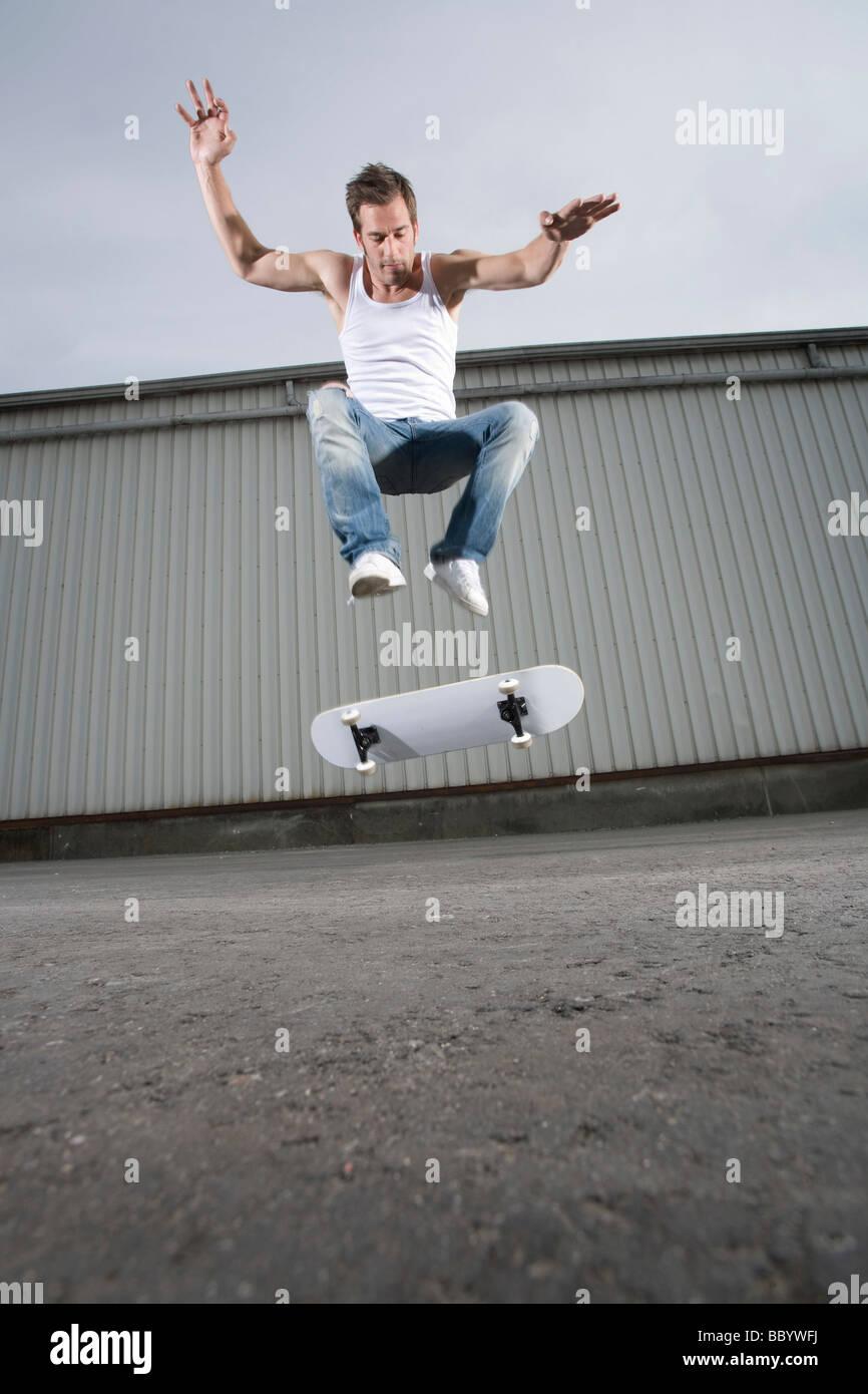 Skateboarder doing a flip trick - Stock Image