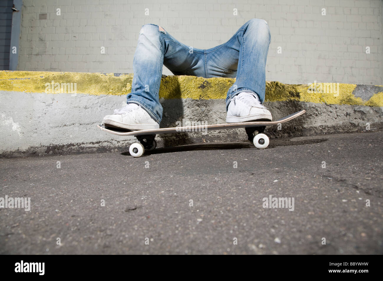 Skateboarder lying on his back, exhausted - Stock Image