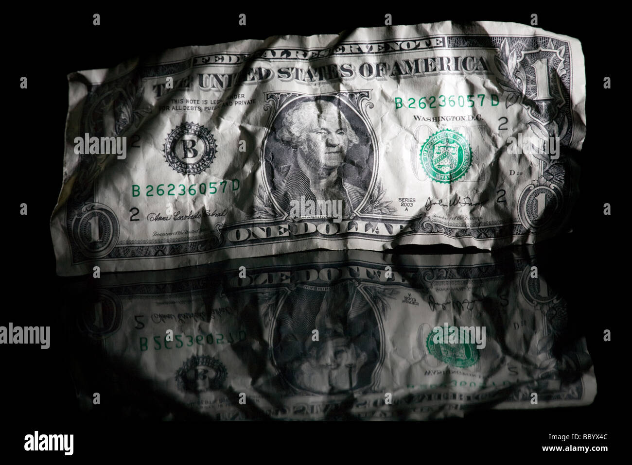crumpled note of one dollar isolated on black glossy background - Stock Image