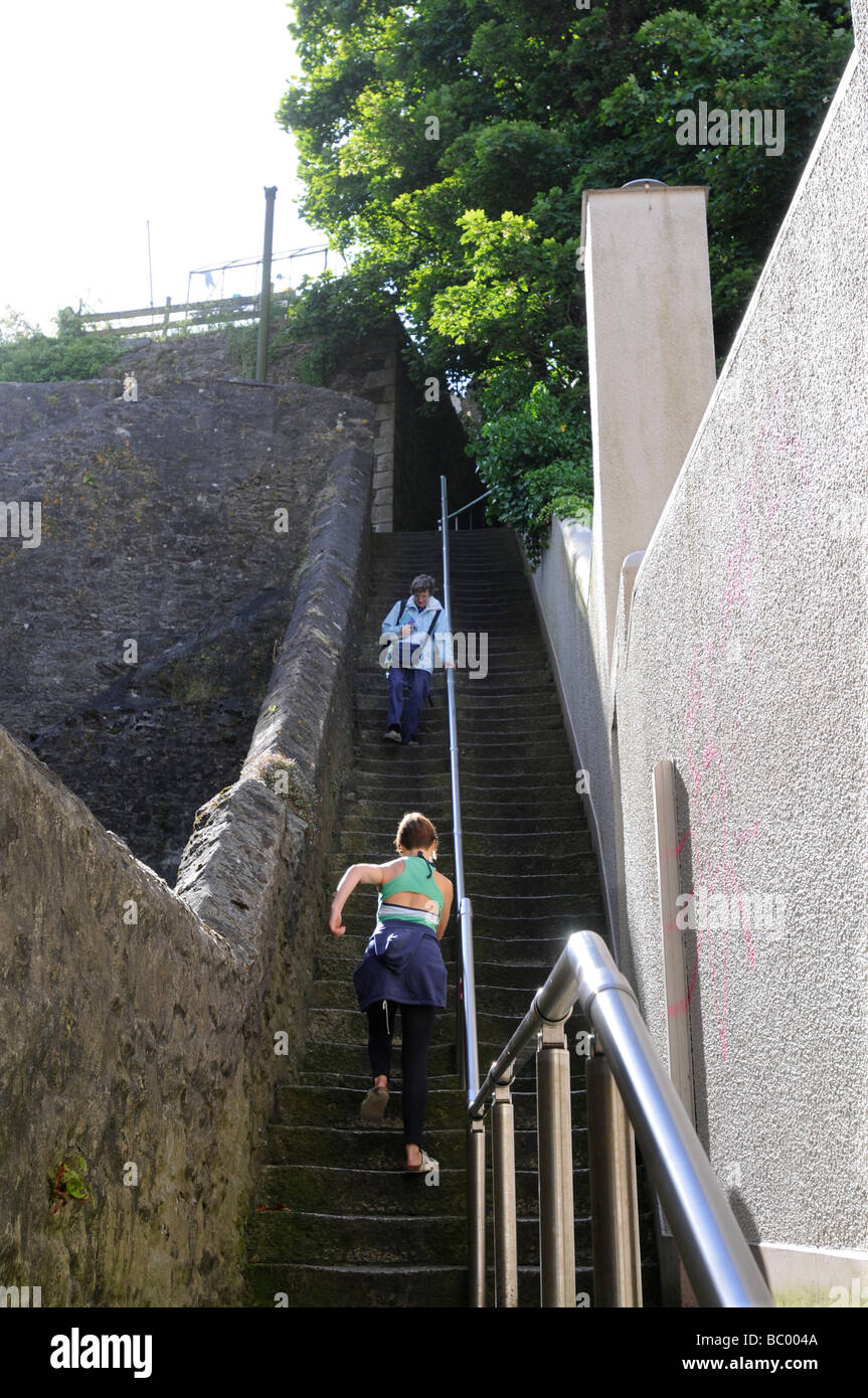 A 40 year old woman climbs a steep flight of stone steps in Falmouth, Cornwall, UK whilst an old lady descends. - Stock Image