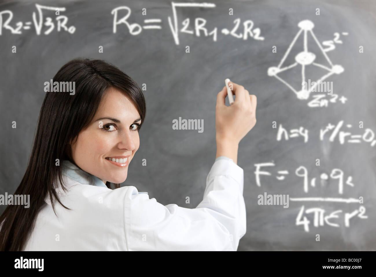 female teacher formulas writing on blackboard - Stock Image