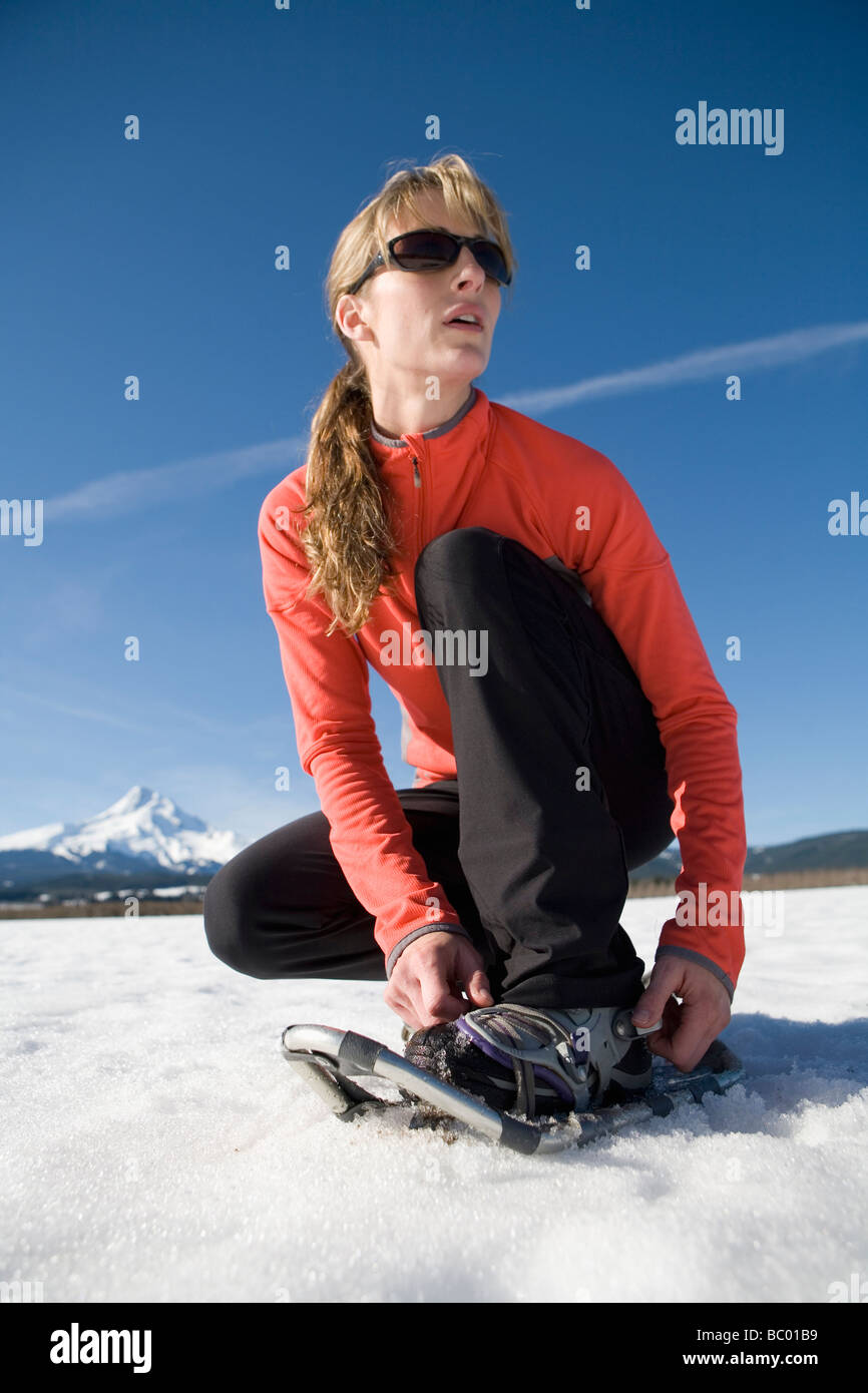 Young woman straps on snowshoes with Mt. Hood, Oregon in background. - Stock Image