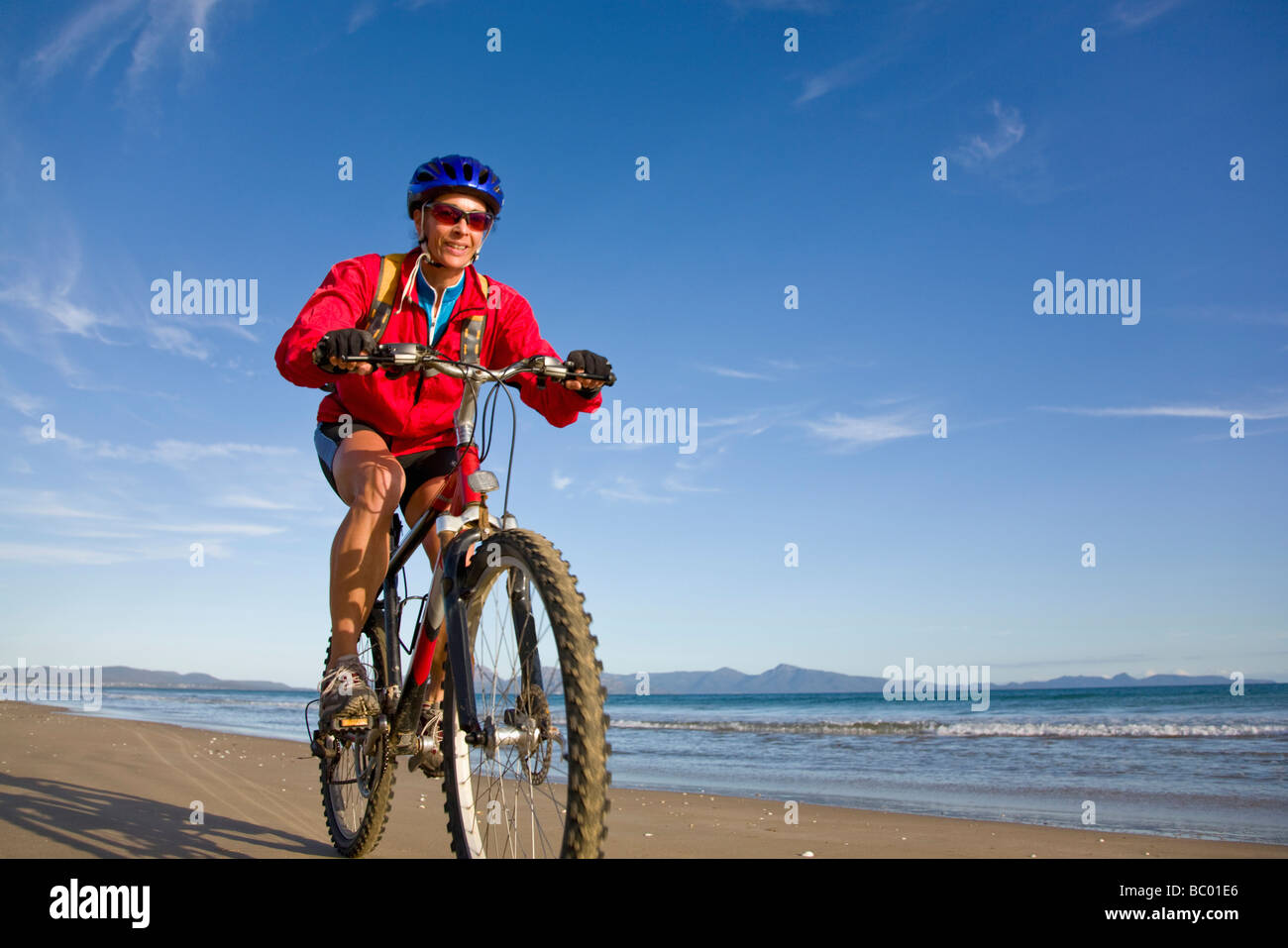 A woman enjoying a bike ride on Nine Mile Beach on the east coast of Tasmania, Australia. - Stock Image