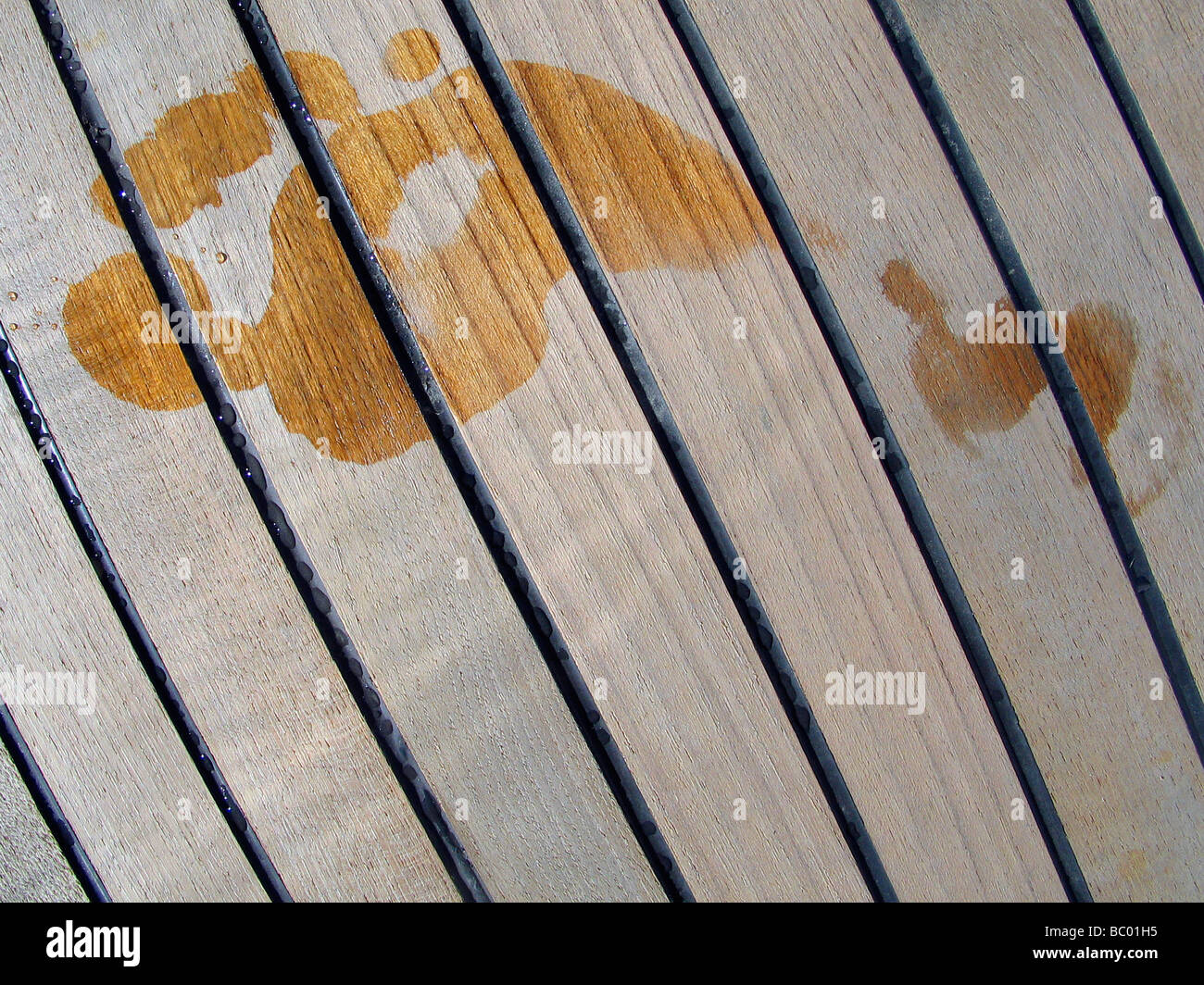 Wet footprint on the teak deck of a yacht. - Stock Image