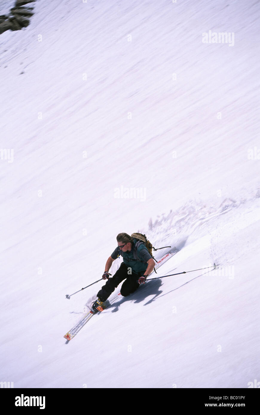 Male telemark skier ripping the spring slopes of Beartooth Pass on Montana on the Wyoming border near Yellowstone - Stock Image