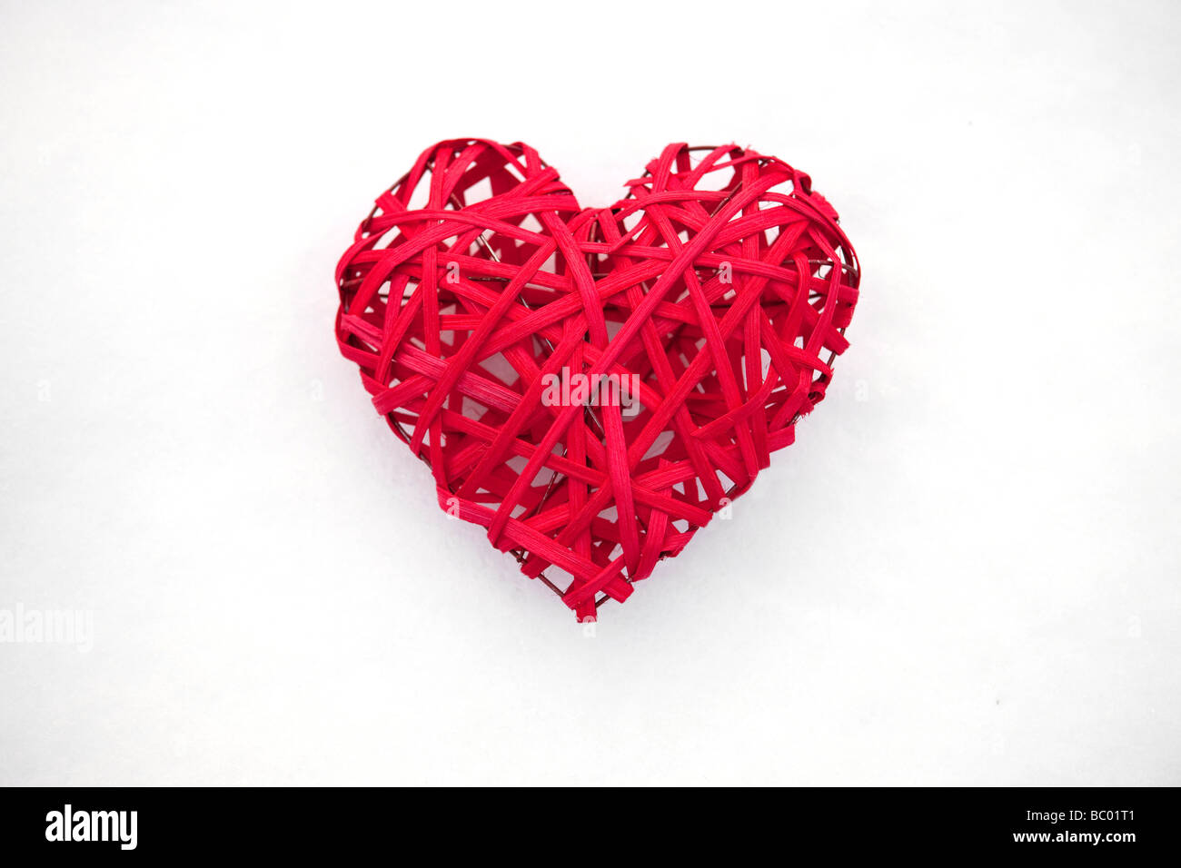 Red Valentine heart on white snow - Stock Image