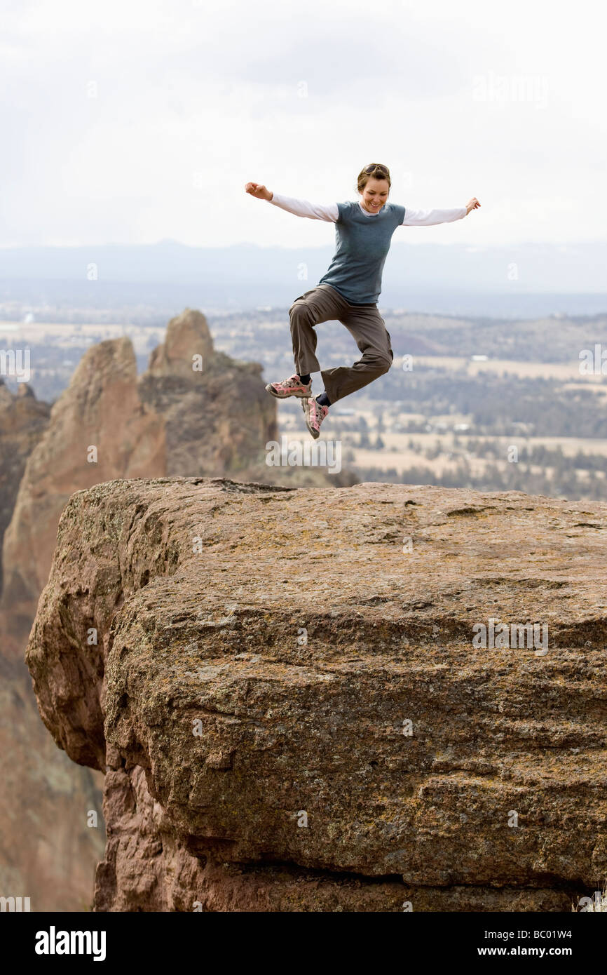 A woman in an 'I Love Green' shirt jumps for joy near the edge of the cliff in Smith Rock, Oregon. - Stock Image