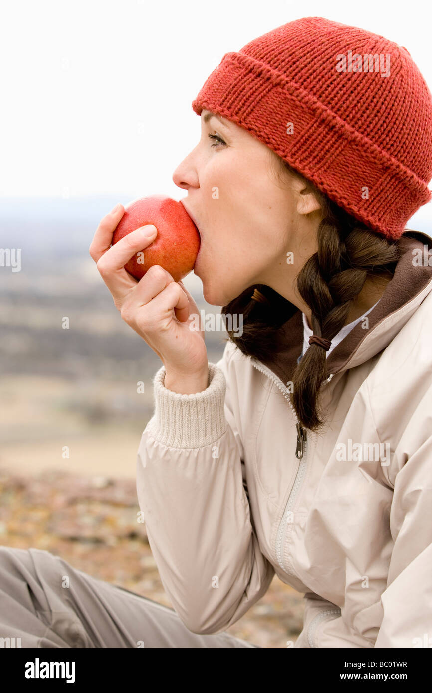 A woman in a red hat and pig tails takes a big bite of a red apple. - Stock Image