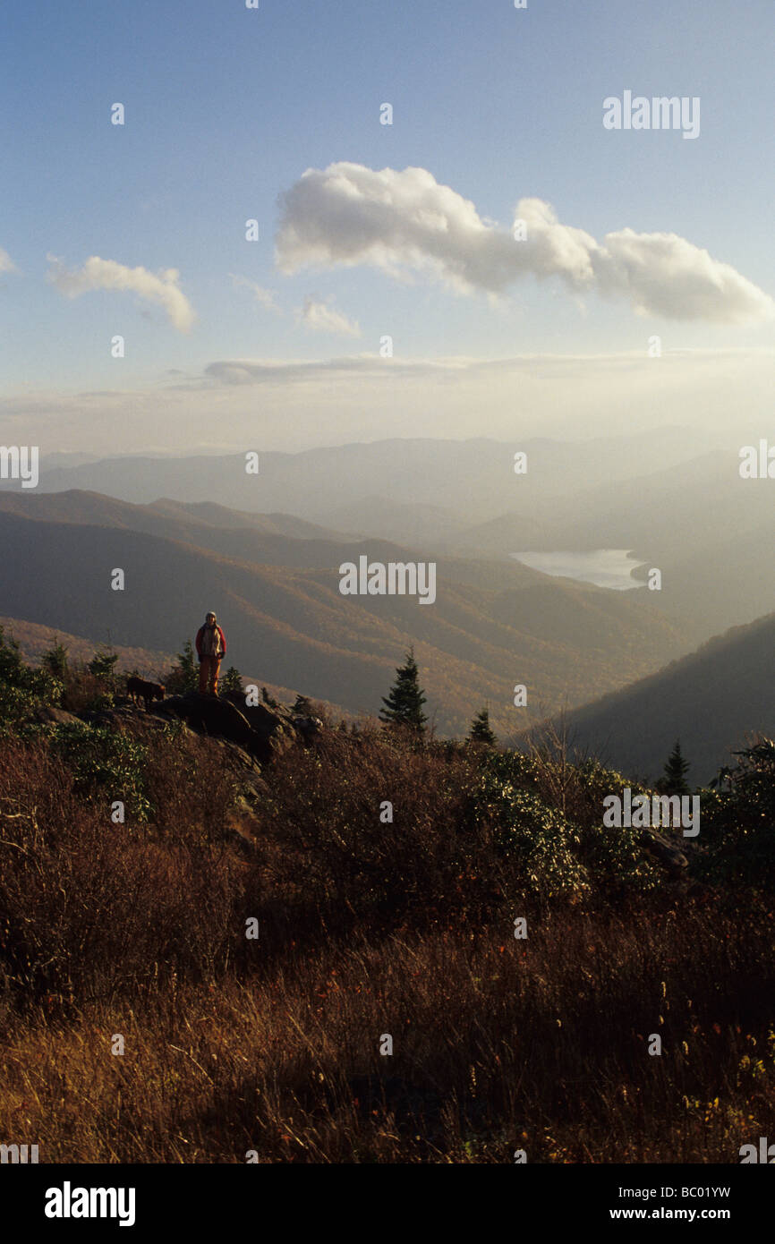 Young female dayhiker soaks in the sunset views near Asheville, North Carolina. - Stock Image