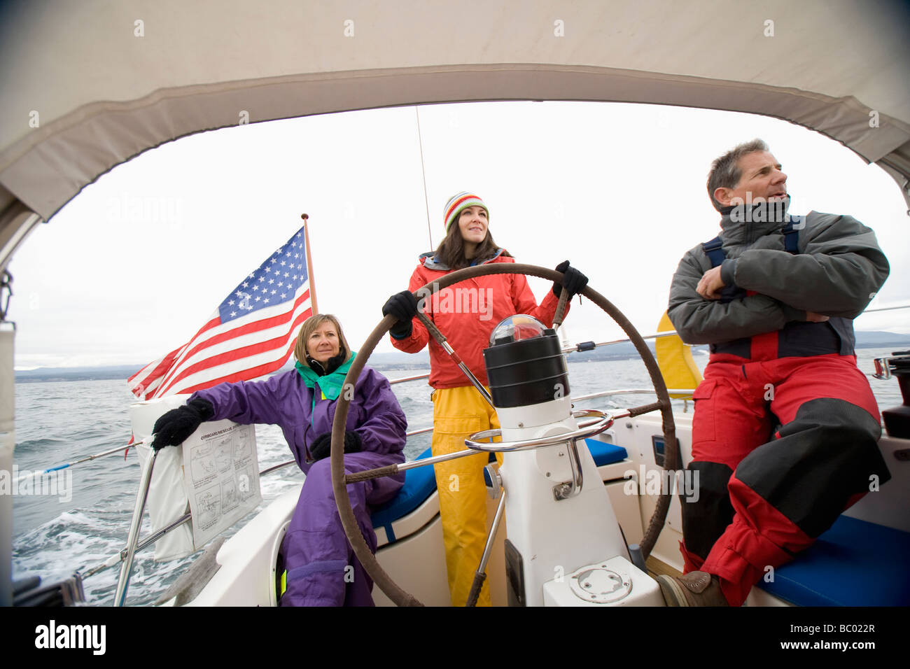 Three people in bright colored sailing gear out at sea. - Stock Image