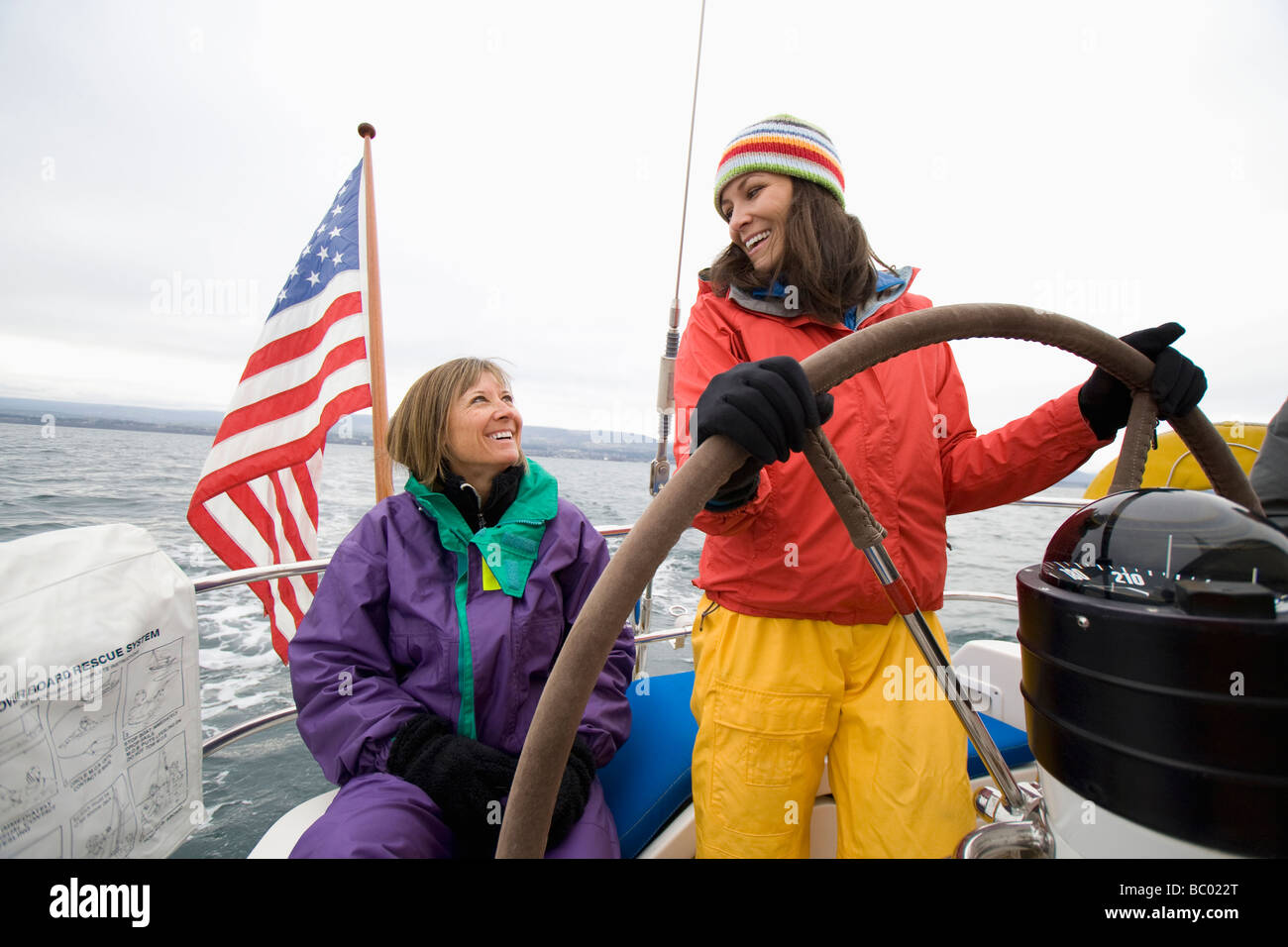 Two smiling women in sailing gear steer a sailboat on a cloudy day. - Stock Image