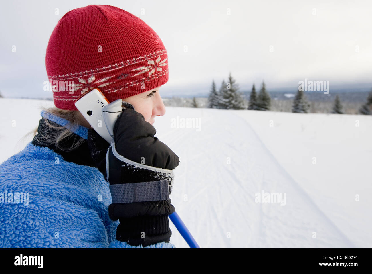 A young woman talking on a cell phone while cross-country skiing. - Stock Image