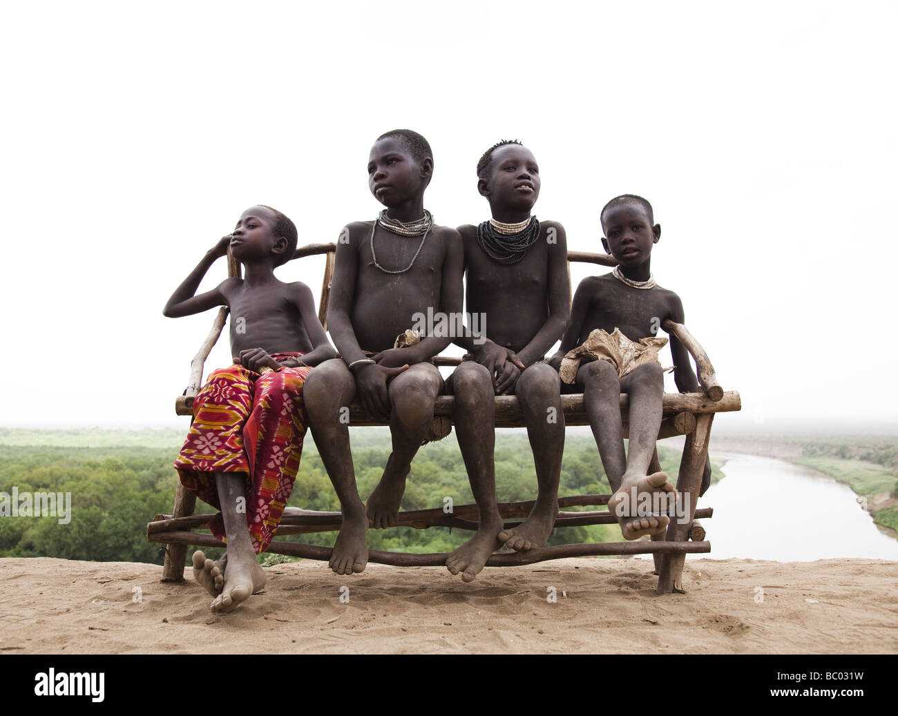 Four young boys sit on a bench overlooking the Omo River in the remote Omo Valley, Ethiopia. - Stock Image