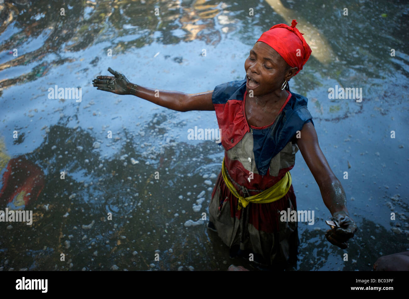 A voodoo priestess sings during a voodoo festival in a mud pit in Haiti. - Stock Image