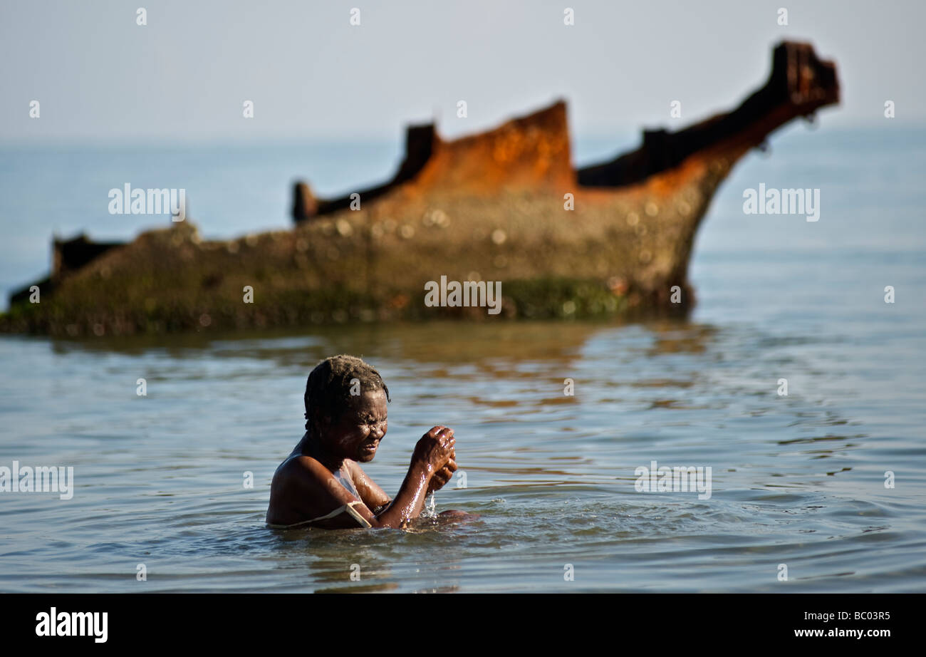 A woman bathes in the ocean in front of the rusted wreckage of a ship during a voodoo festival in Haiti. - Stock Image