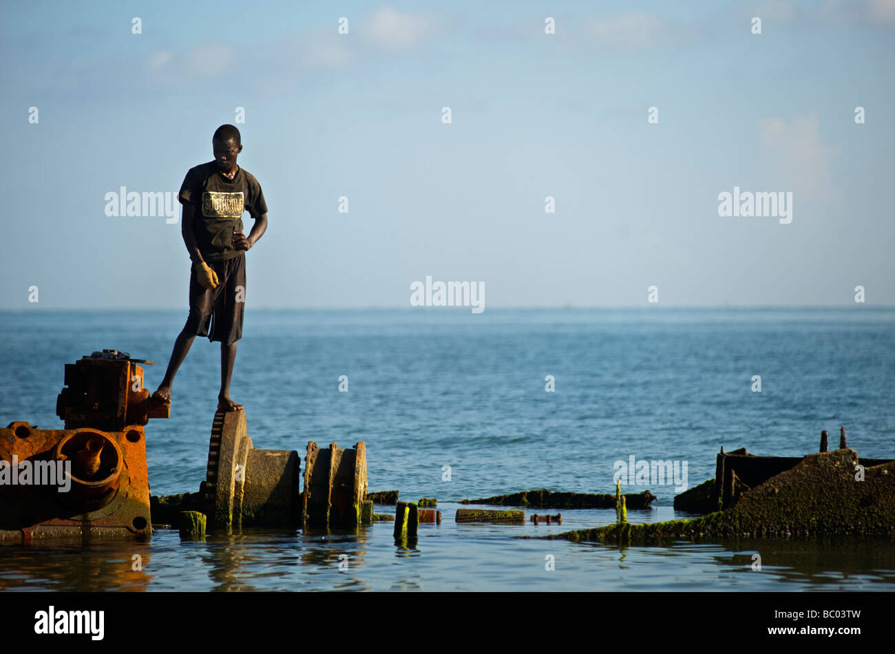 A young man stands atop beached wreckage of a former vessel at Bord de Mer de Limonade, Haiti. - Stock Image