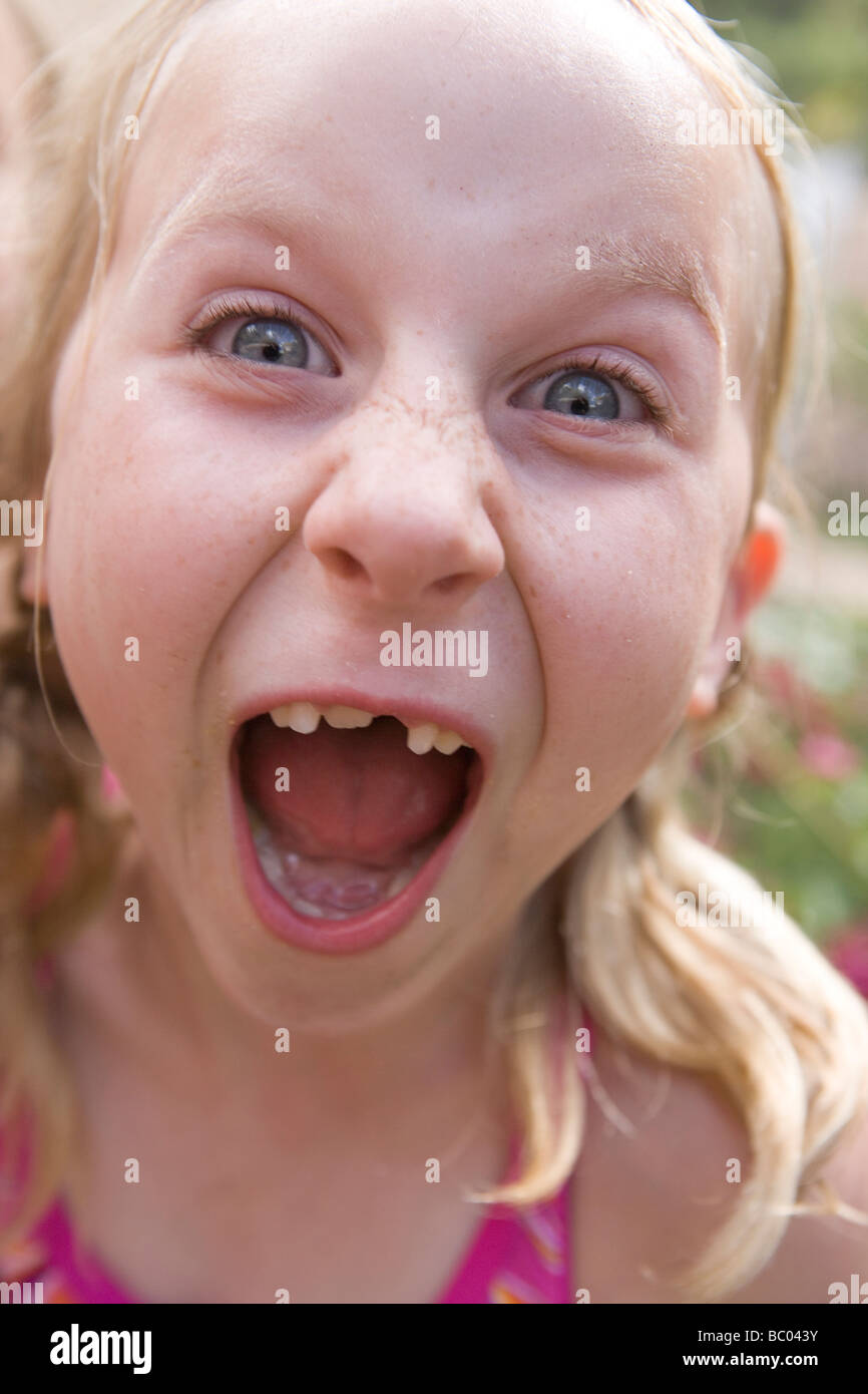 seven year old girl screaming into the camera, wearing pink swimsuit, backyard, summer - Stock Image