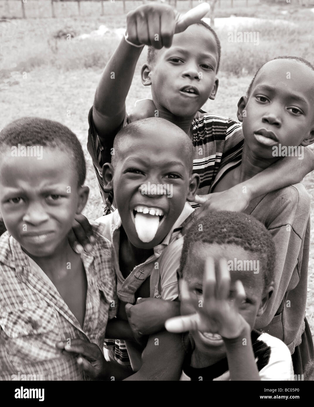 Black and white photograph of gambian african boys pulling faces and messing about for the camera