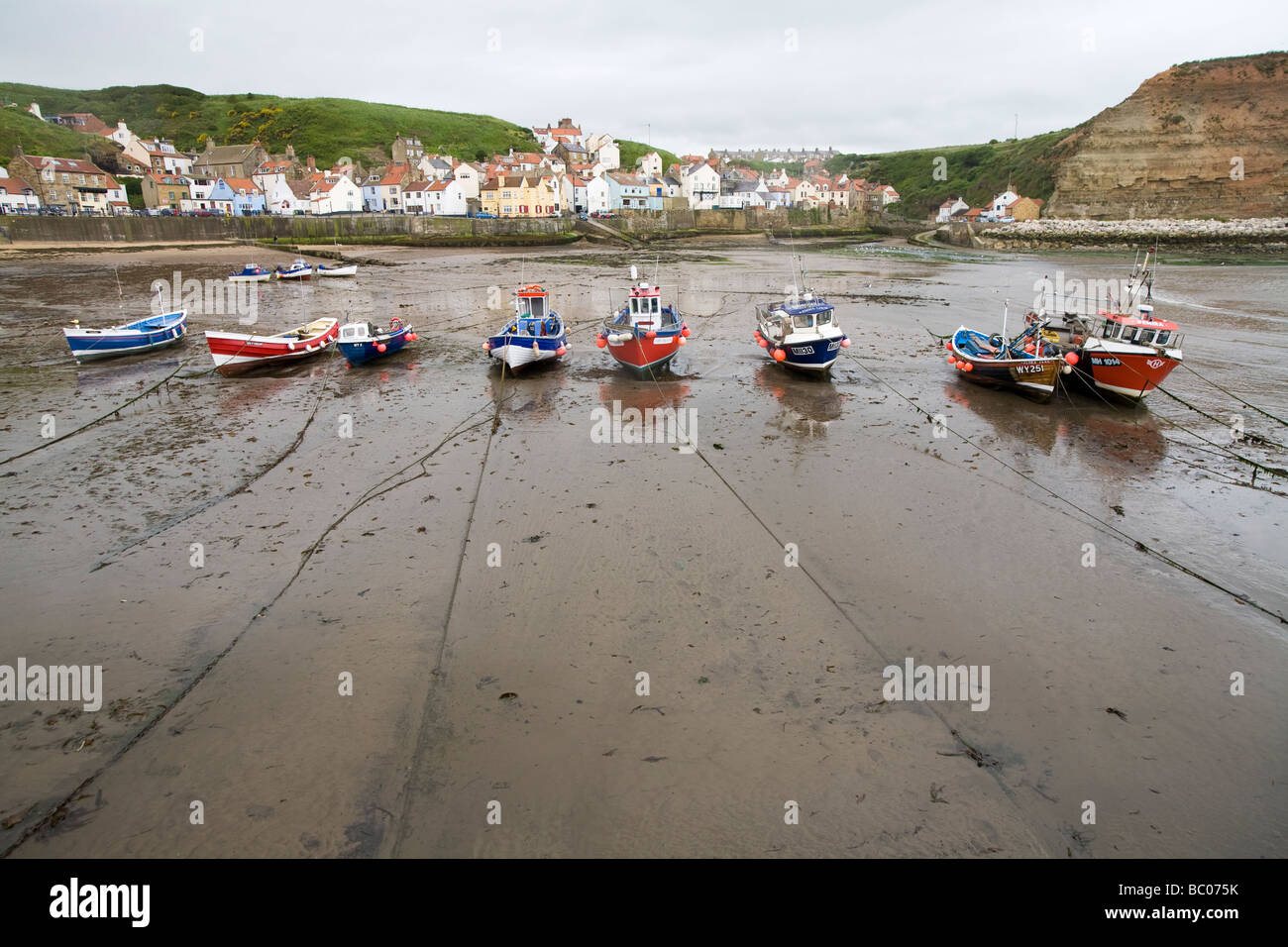Small tied-up boats in a row left dry at low tide standing on sand with reflections Staithes North Yorkshire England - Stock Image
