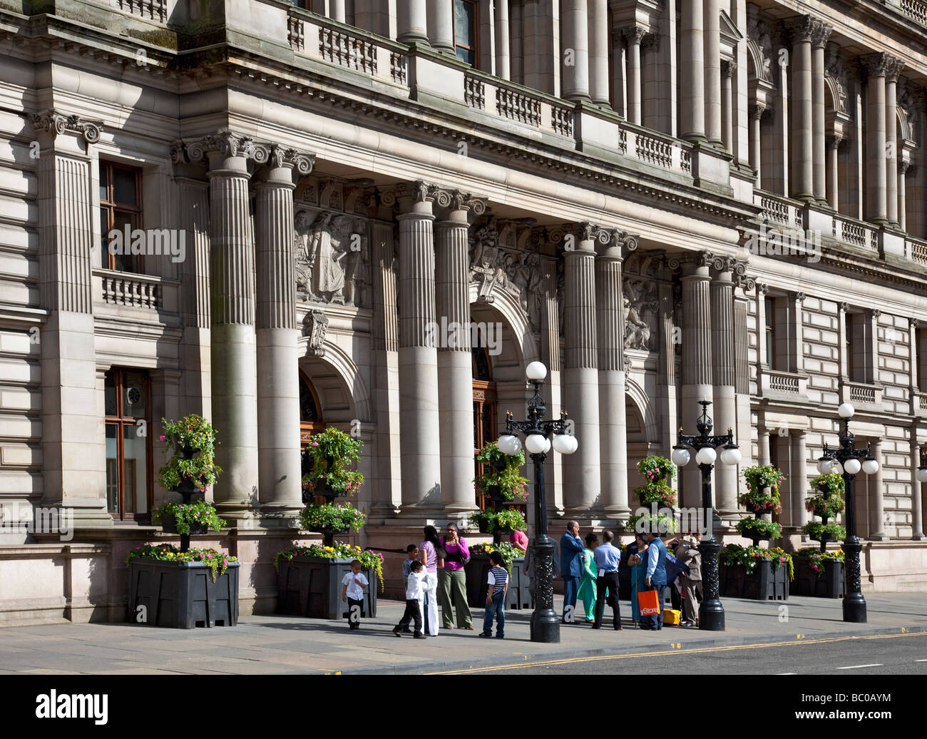 A group of Asian visitors outside Glasgow City Chambers in George Square, Glasgow. - Stock Image