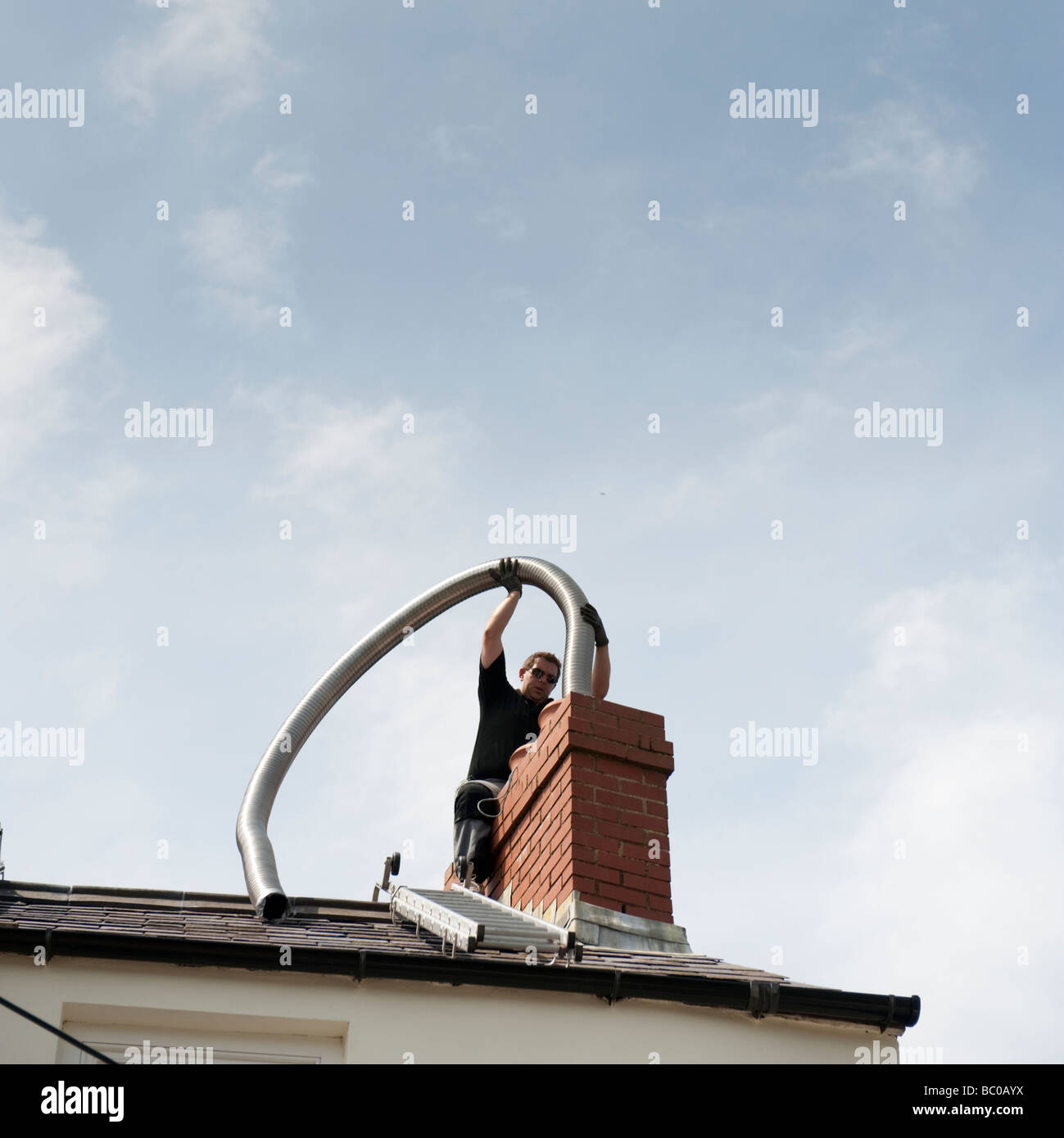 A man installing flexible metal chimney flue liner to a house in Little Haven Pembrokeshire Wales UK - Stock Image