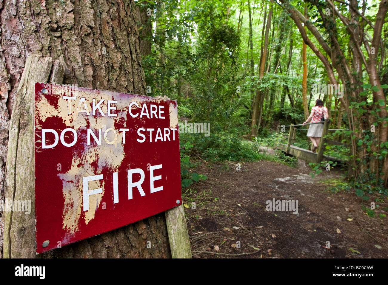 Woman walks past a sign that says Take Care Do Not Start Fire on a forest walk - Stock Image