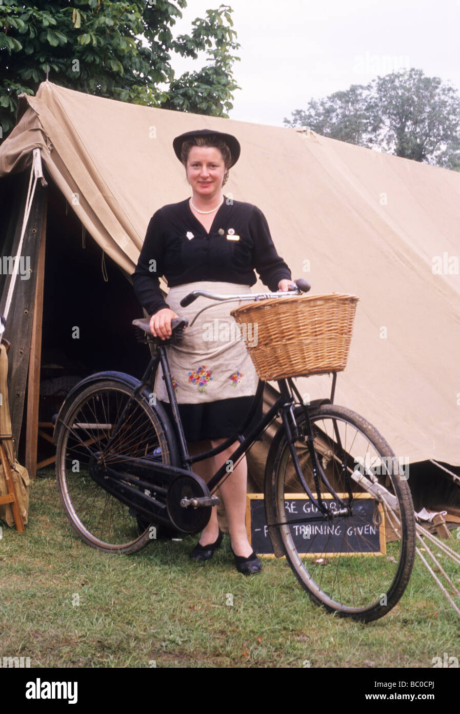 2nd World War historical re-enactment lady woman female civilian landgirl ATS WVS bicycle bike tent land girl British - Stock Image