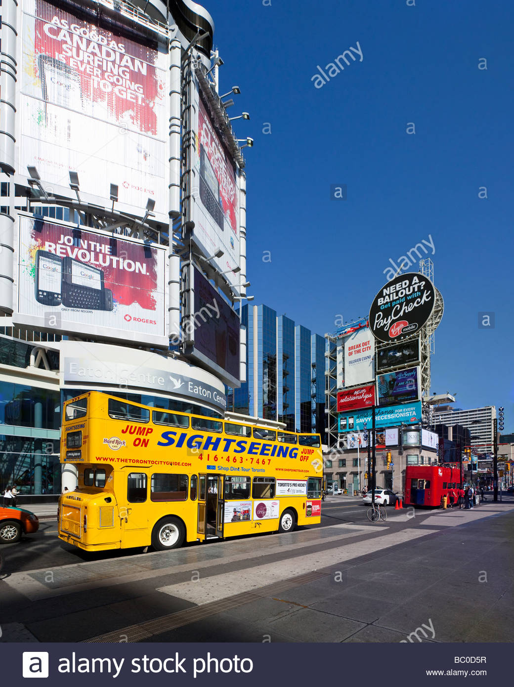 Sightseeing bus and media tower at Yonge Dundas Square a public square in Toronto Ontario Canada - Stock Image