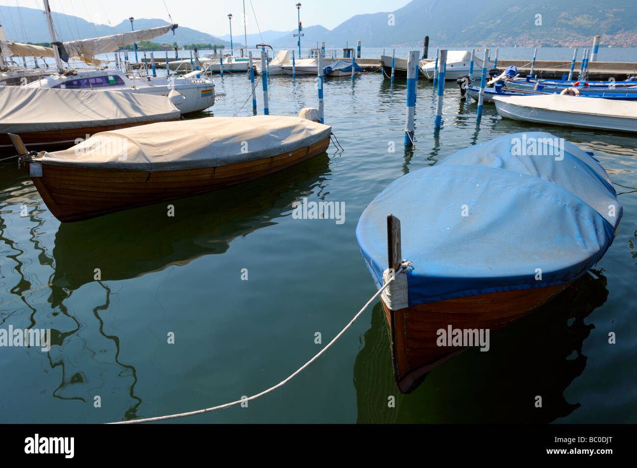 Covered boats moored in the marina at Iseo Brescia Lombardy Italy protected from the weather by tarpaulin - Stock Image