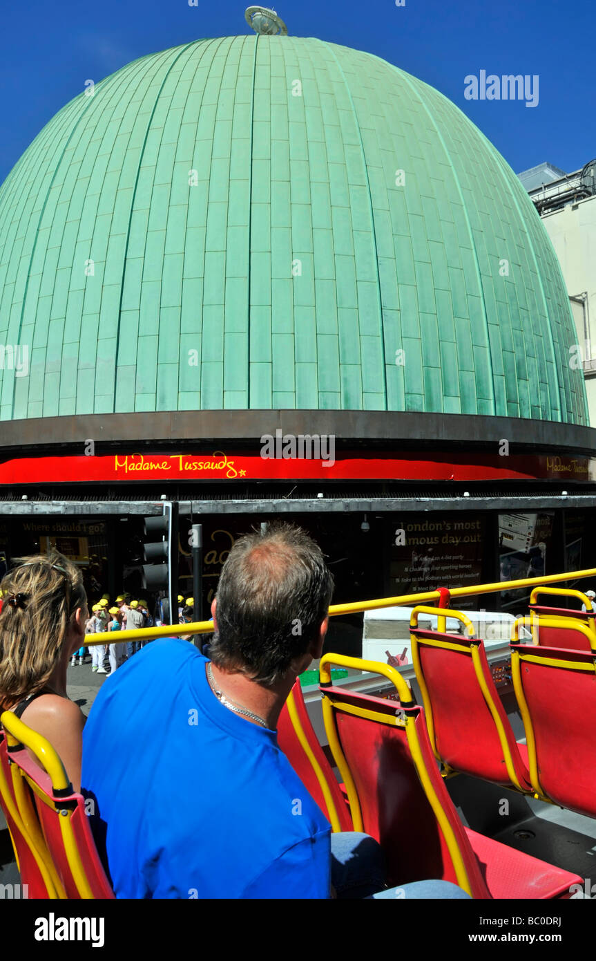 London top deck of open top tour bus passengers with view of Madame Tussauds famous wax museum & Planetarium - Stock Image