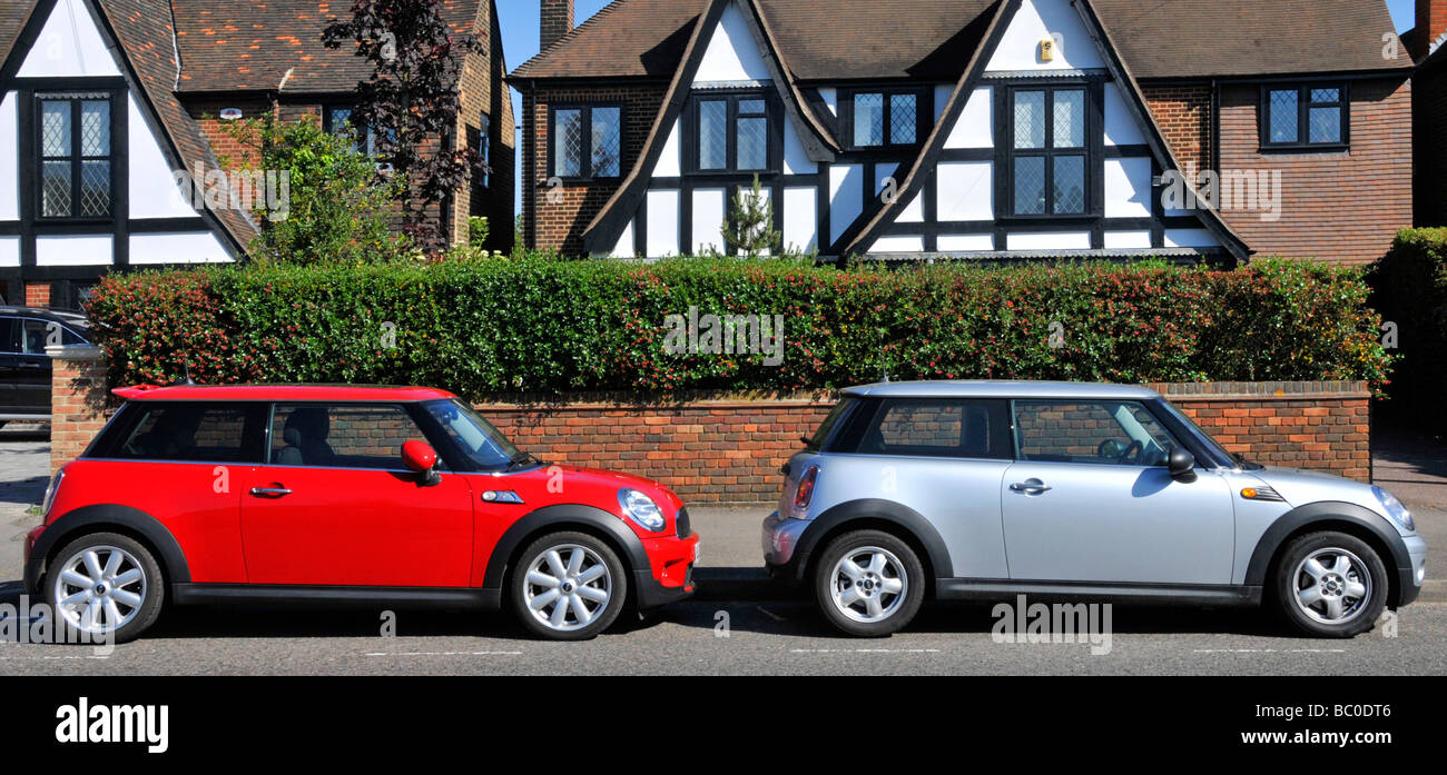 Two of a kind BMW mini cars parked in residential road - Stock Image