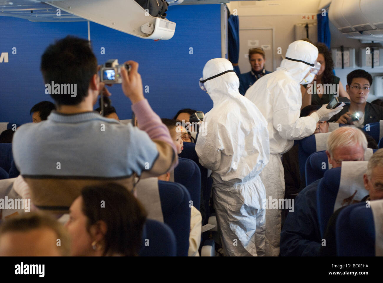 Medical workers aboard the plane from Amsterdam check passengers for signs of fever (swine flu) after landing at - Stock Image