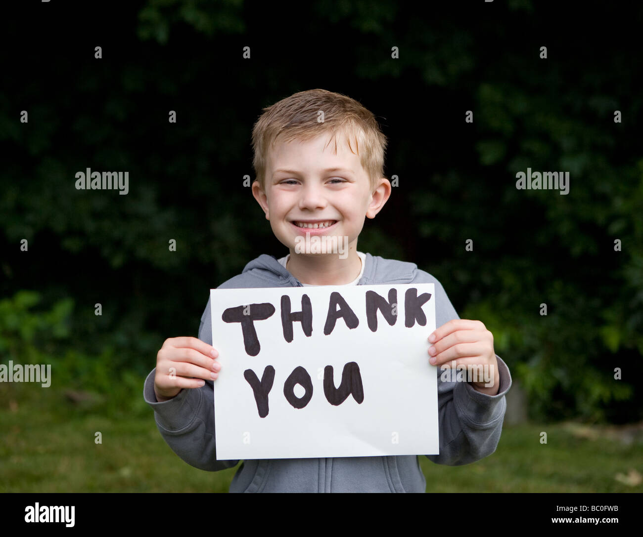 Young boy smiling with Thank You written on a paper - Stock Image