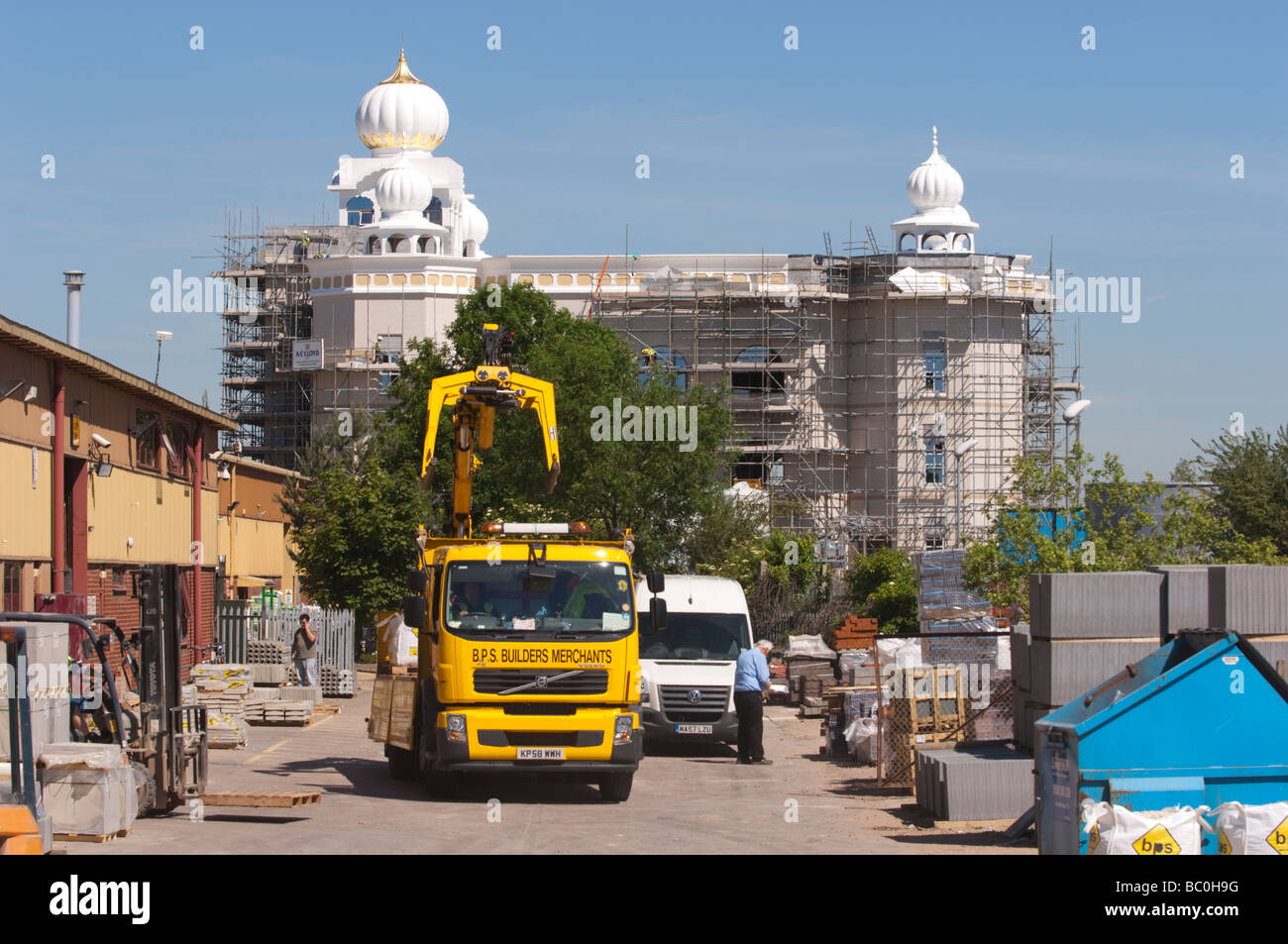 Builders merchants with Gurdwara Sikh Temple construction site behind, Leamington Spa, Warwickshire, UK. - Stock Image