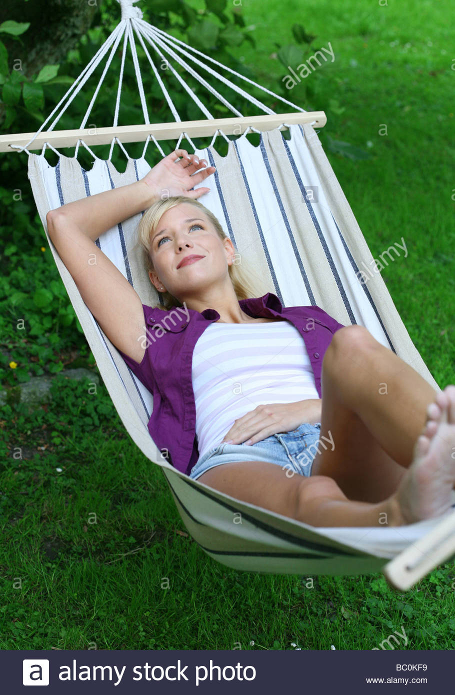 young blond woman relaxing in hammock Stock Photo