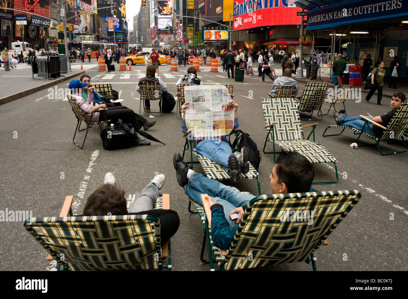 Tourists relax in lawn chairs in the new car-free Broadway Plaza in Times Square - Stock Image